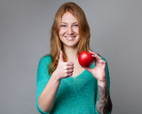 Portrait d'une jeune dame de gingembre dans le chemisier de turquoise avec un APPL Photographie stock libre de droits