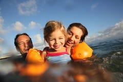 Portrait d'une jeune famille nageant ensemble Photographie stock