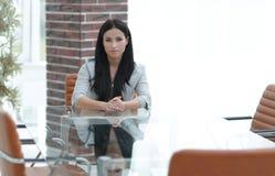 Portrait d'une jeune femme d'affaires s'asseyant à une table dans une salle de conférence Images stock
