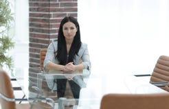 Portrait d'une jeune femme d'affaires s'asseyant à une table dans une salle de conférence Images libres de droits