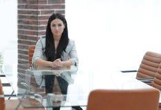 Portrait d'une jeune femme d'affaires s'asseyant à une table dans une salle de conférence Photo stock