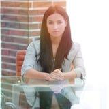 Portrait d'une jeune femme d'affaires s'asseyant à une table dans une salle de conférence Photographie stock