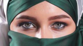 Portrait d'une jeune femme arabe avec ses beaux yeux dans le niqab islamique traditionnel de tissu banque de vidéos