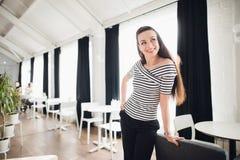 Portrait d'une jeune femme attirante avec de longs cheveux droits semblant partis tout en se penchant contre une chaise dans un c Image libre de droits