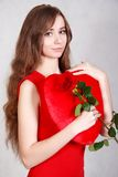 Portrait d'une jeune femme attirante avec un oreiller en forme de coeur Photographie stock