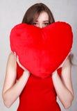 Portrait d'une jeune femme attirante avec un oreiller en forme de coeur Photos libres de droits