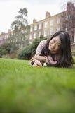 Portrait d'une jeune femme avec la pelouse menteuse de fleur devant le bâtiment Image libre de droits