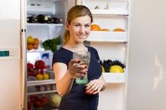 Portrait d'une jeune femme avec le verre de l'eau devant le réfrigérateur complètement de la nourriture Photographie stock
