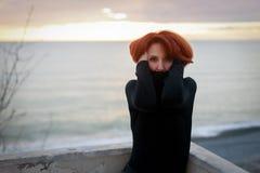 Portrait d'une jeune femme avec les cheveux rouges et de regard perçant sur le fond de la mer et du coucher du soleil photos libres de droits