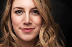 Portrait d'une jeune femme blonde attirante sur un fond noir images stock