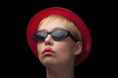 Portrait d'une jeune femme blonde avec le chapeau rouge et les verres noirs photographie stock