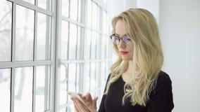 Portrait d'une jeune femme blonde en verres avec un téléphone à la grande fenêtre photographie stock