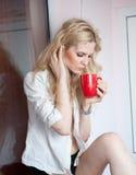 Portrait d'une jeune femme blonde tenant une tasse rouge utilisant une chemise blanche avec une expression d'être tristesse Femel Images stock