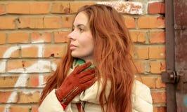 Portrait d'une jeune femme châtain se tenant prêt le mur de briques Photos libres de droits