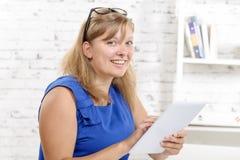 Portrait d'une jeune femme d'affaires avec du charme, avec le comprimé Photo stock
