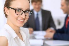 Portrait d'une jeune femme d'affaires contre un groupe de gens d'affaires lors d'une réunion Photos libres de droits