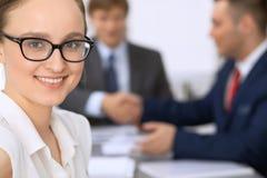 Portrait d'une jeune femme d'affaires contre un groupe de gens d'affaires lors d'une réunion Image stock