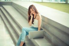 Portrait d'une jeune femme d'affaires occasionnelle à l'aide de l'ordinateur portable Photographie stock libre de droits