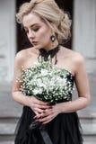 Portrait d'une jeune femme dans la robe noire avec des fleurs mariage Photo libre de droits