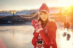 Portrait d'une jeune femme dans un chapeau sur la patinoire, un sourire sur son visage, le soleil photographie stock libre de droits