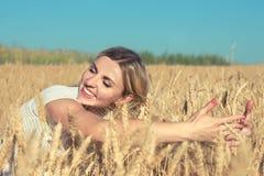 Portrait d'une jeune femme dans un domaine de blé, contacts l'épillet d'or image stock