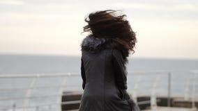 Portrait d'une jeune femme de brune dans le manteau de fourrure fonctionnant par la mer ou l'océan en hiver tournant autour et so banque de vidéos