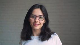 Portrait d'une jeune femme de brune dans les verres et les accolades sur ses dents souriant à l'appareil-photo clips vidéos