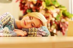 Portrait d'une jeune femme de sommeil sur la table Image stock