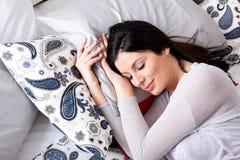 Portrait d'une jeune femme enceinte tout en dormant dans un underwea images stock