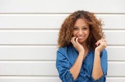 Portrait d'une jeune femme gaie posant avec la main dans les cheveux Image libre de droits