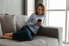 Portrait d'une jeune femme heureuse à l'aide du téléphone portable image stock