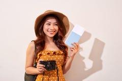 Portrait d'une jeune femme heureuse dans la caméra de participation de chapeau et le passeport de représentation tout en se tenan photographie stock