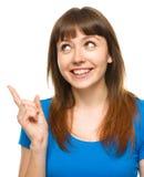 Portrait d'une jeune femme indiquant la gauche Photographie stock