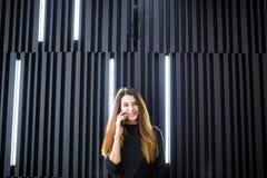 Portrait d'une jeune femme parlant au téléphone portable contre le mur moderne de bureau Images libres de droits