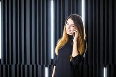 Portrait d'une jeune femme parlant au téléphone portable contre le mur moderne de bureau Photo libre de droits