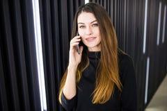 Portrait d'une jeune femme parlant au téléphone portable contre le mur moderne de bureau Photo stock