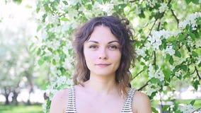 Portrait d'une jeune femme parmi des pommiers en gros plan banque de vidéos