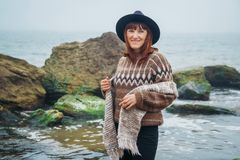Portrait d'une jeune femme rousse dans un chapeau et une écharpe dans la perspective des roches contre la belle mer photographie stock