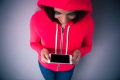Portrait d'une jeune femme se tenant avec le smartphone photos stock