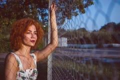Portrait d'une jeune femme très jolie près d'une barrière Coucher du soleil Copyspace image libre de droits