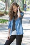Portrait d'une jeune fille avec de longs cheveux avec le bracelet sur son bras dans la chemise de denim Photographie stock libre de droits