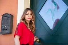 Portrait d'une jeune fille blonde sur un fond d'une porte de maison verte image libre de droits