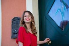 Portrait d'une jeune fille blonde sur un fond d'une porte de maison verte photographie stock libre de droits