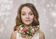 Portrait d'une jeune fille dans un collier des roses Photographie stock