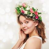 Portrait d'une jeune fille de sourire mignonne dans une guirlande des roses Photographie stock