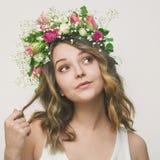 Portrait d'une jeune fille espiègle dans une guirlande des roses Photo libre de droits
