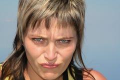 Portrait d'une jeune fille fâchée sur un fond de ciel bleu photographie stock