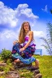 Portrait d'une jeune fille heureuse et d'une maxi jupe florale habill?e avec le dessus photographie stock