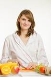 Portrait d'une jeune fille qui coupe des légumes pour des salades Photos libres de droits