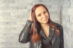 Portrait d'une jeune fille sans maquillage sur son visage dans une veste noire contre un mur de briques gris photo libre de droits